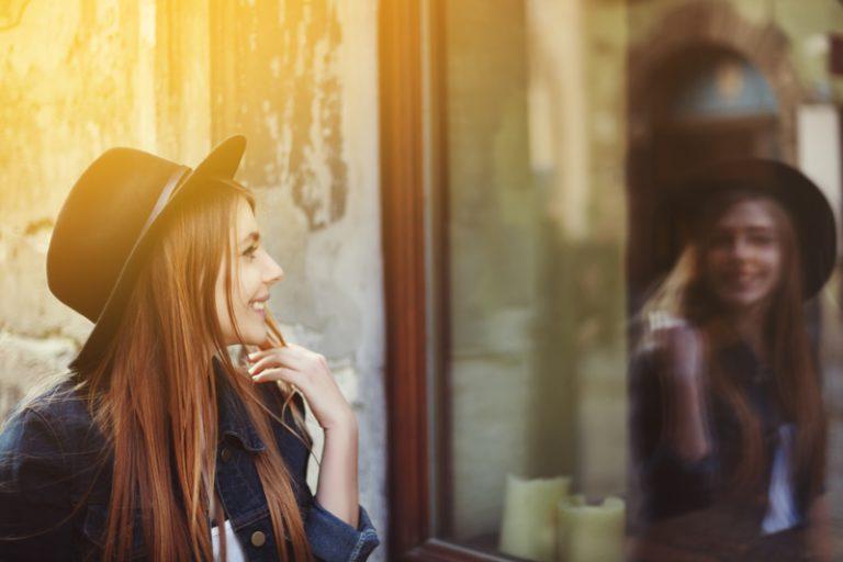 mujer feliz sonriendo con sombrero mirándose en un cristal espejo
