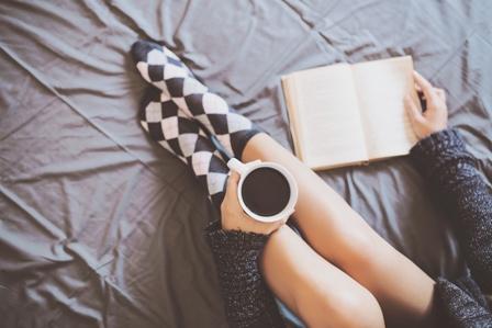pies de mujer en la cama con cafe y libro leyendo y bebiendo con calcetines de cuadros