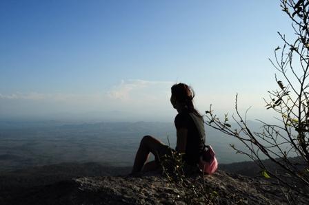 mujer dada la vuelta de espaldas en la montaña mirando al horizonte y al cielo pensando