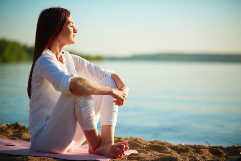 mujer vestida de blanco haciendo yoga pensando meditando en una playa con el mar de fondo