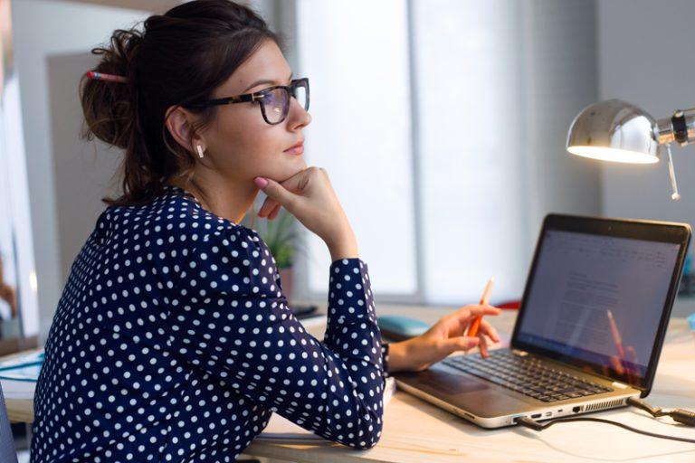 mujer con gafas vestida de lunares azules y blancos pensando y trabajando con un ordenador en una mesa con una lampara