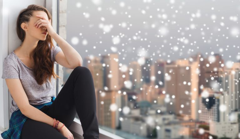 mujer triste con la cara tapada por sus brazos levantados en una ventana nevando con ciudad de fondo