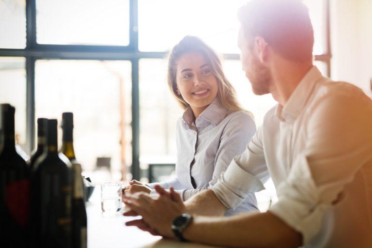 pareja chico y chica mirándose y hablando felices sonriendo en una barra de bar