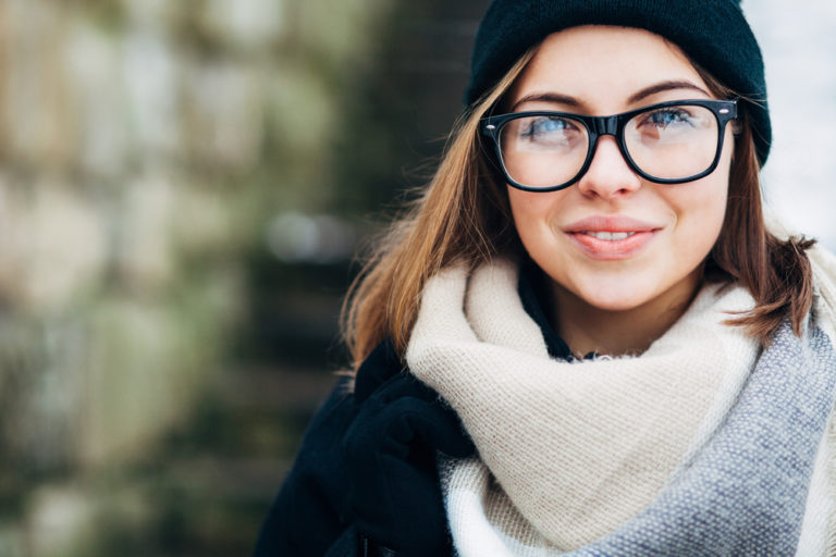 mujer sonriendo feliz con pelo moreno con gafas negras con bufanda blanca y fondo difuminado