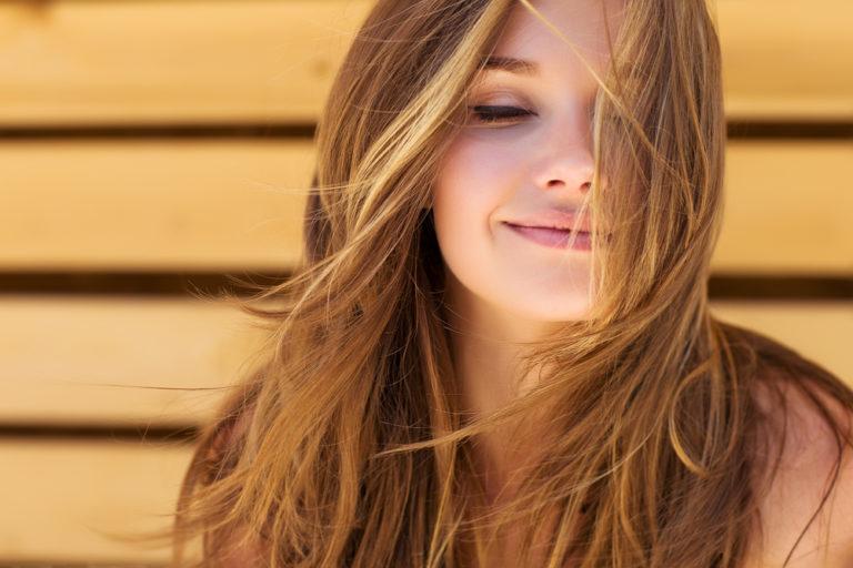 mujer rubia sonriendo con los ojos cerrados pensando con el pelo enla cara y el fondo de madera