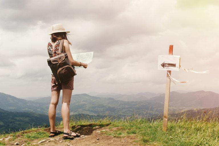 mujer dada la vuelta de espaldas en el campo encima de la montaña mirando un mapa para no perderse y guiarse