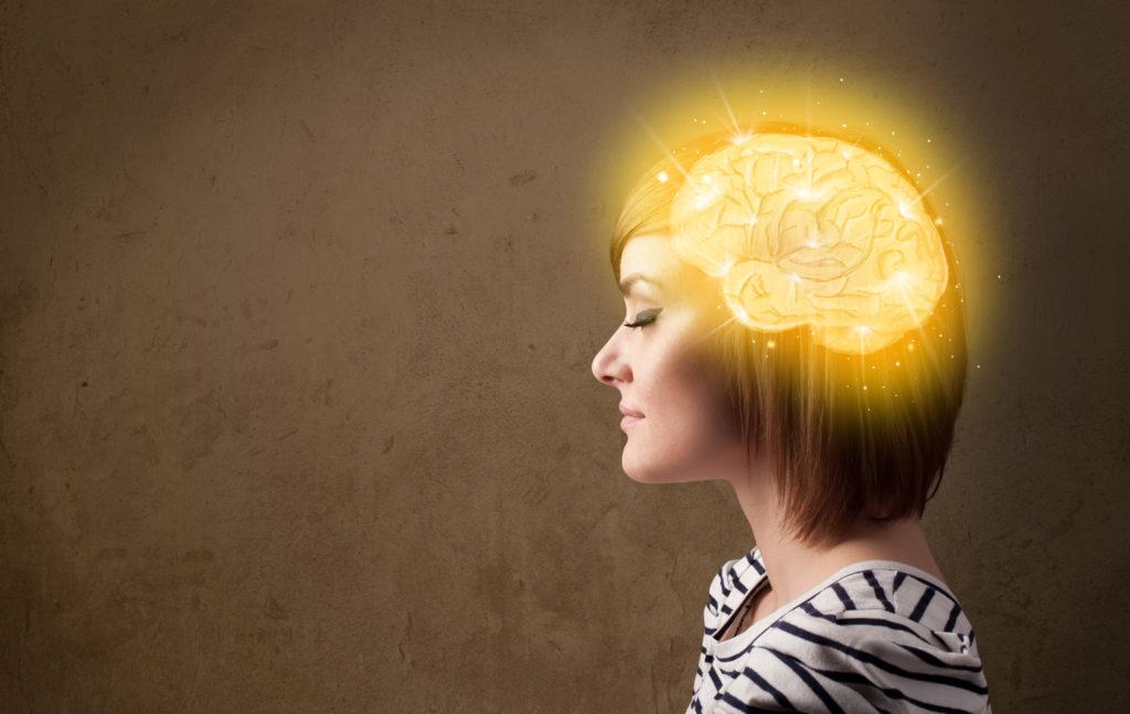mujer morena con cerebro brillando de oro dorado pensando con fondo marrón