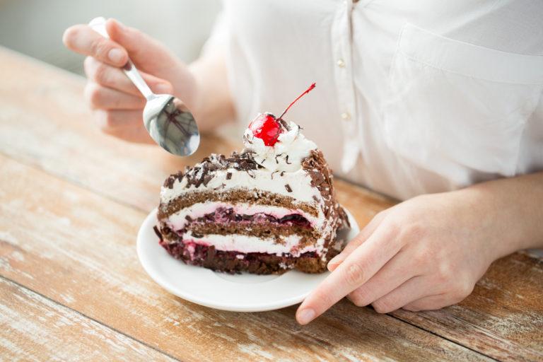 persona mujer vestida de blanco comiendo una tarta de chocolate con cereza guinda del pastel con cuchara sobre una mesa de madera