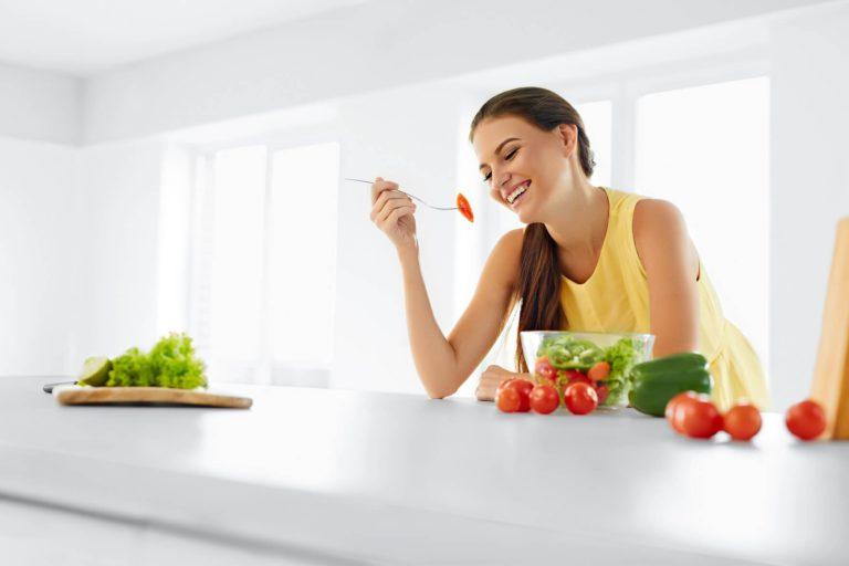 mujer vestida de amarillo comiendo verduras y frutas en cocina blanca y fondo blanco