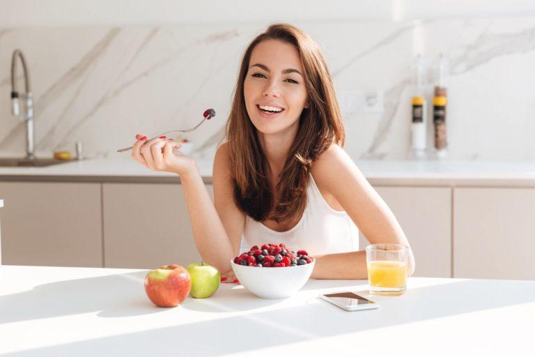 mujer morena comiendo fruta y bebiendo zumo en mesa blanca y fondo blanco