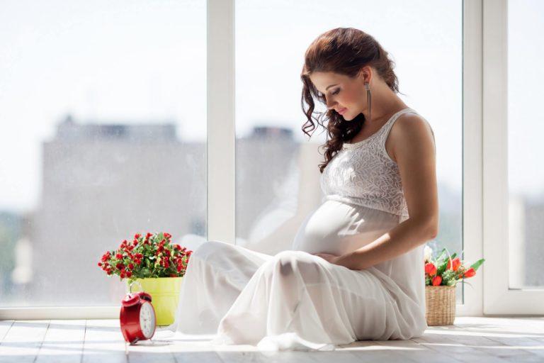mujer con vestido blanco embarazada con flores rojas y despertador