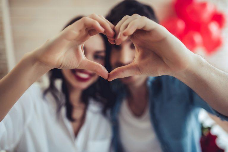 pareja feliz dandose la mano haciendo un corazón