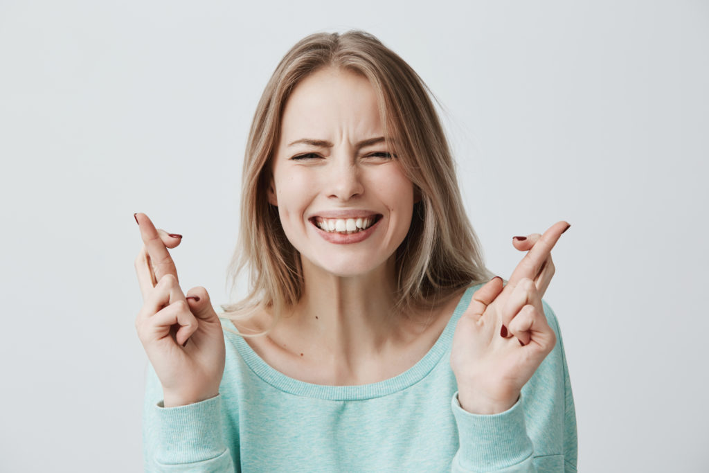 mujer rubia cruzando los dedos pidiendo suerte con fondo balnco gris claro