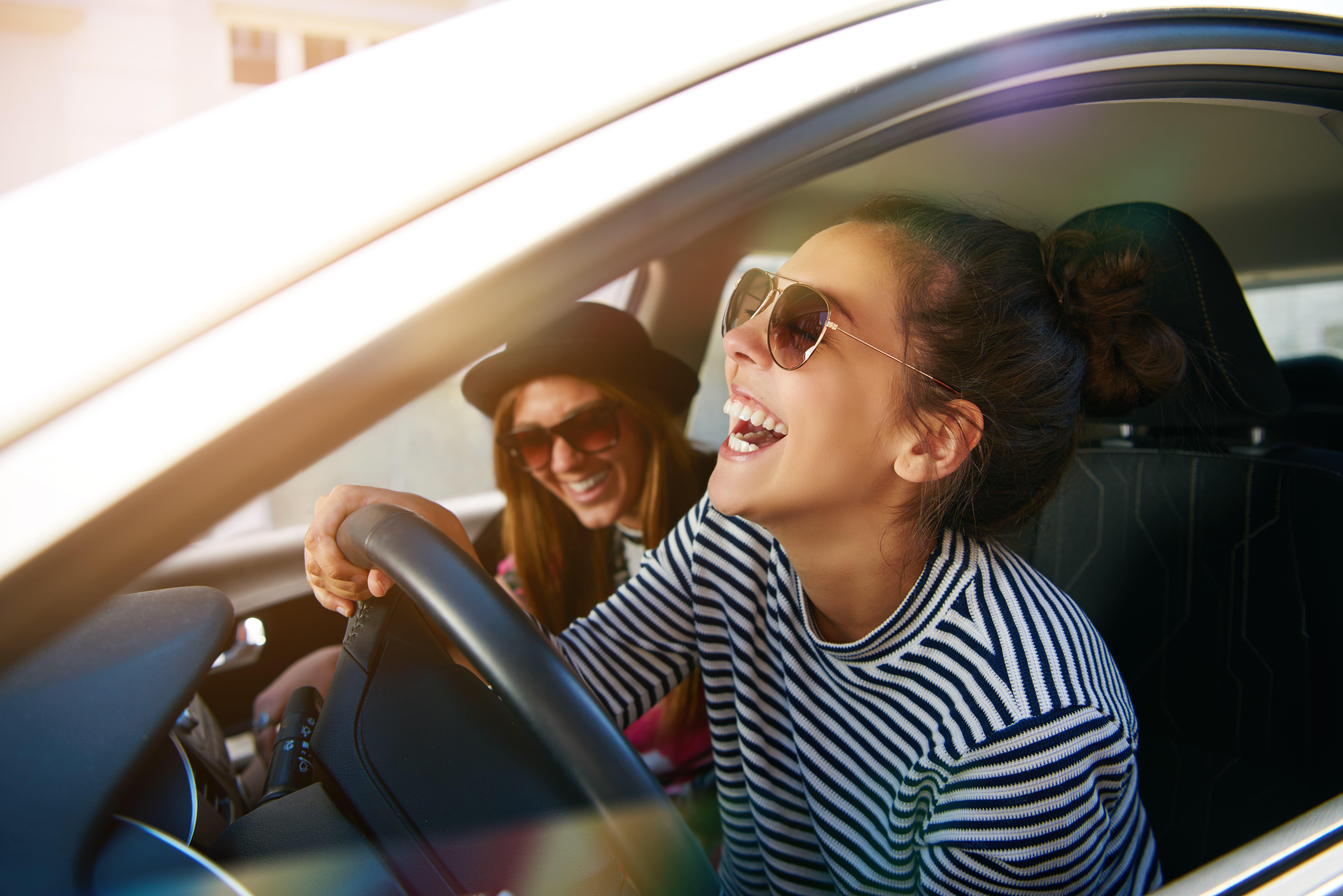dos chicas con gafas de sol en un coche felices riendose y disfrutando del viaje trayecto