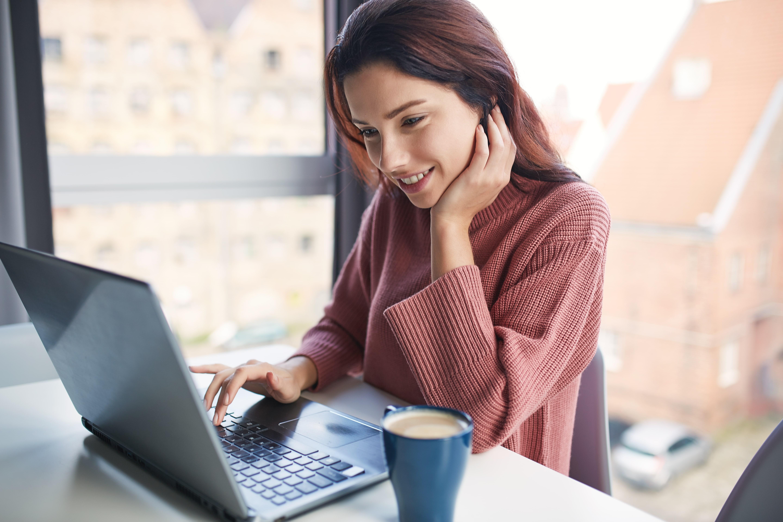 mujer contenta feliz y pelirroja utilizando el ordenador y tomando un cafe por la mañana en una mesa