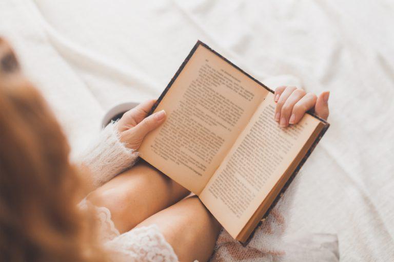 mujer leyendo en la cama sentada