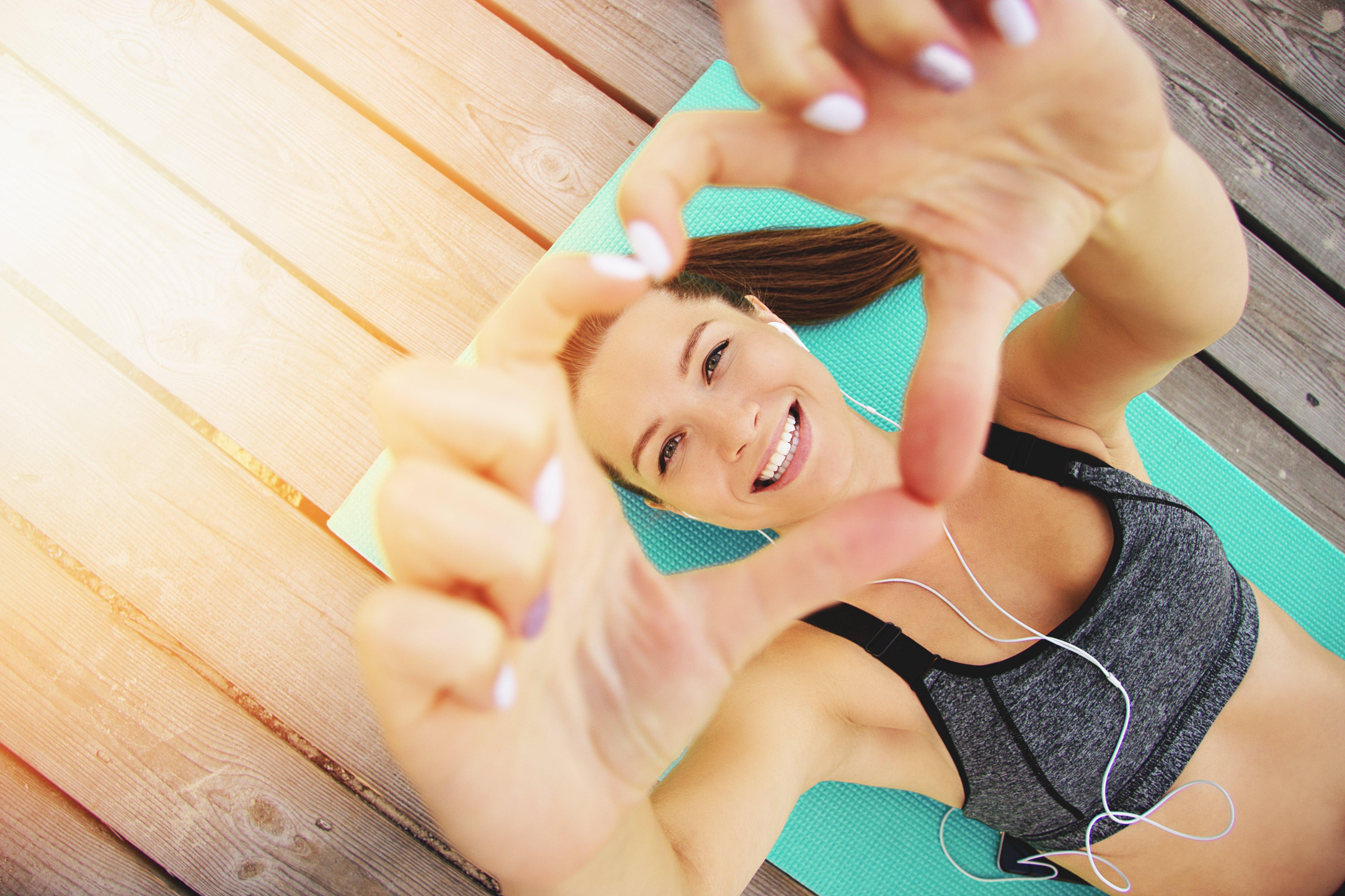 mujer tumbada en el suelo haciendo deporte en una esterilla de yoga o zumba con los brazos levantadoshaciendo la forma de un corazón con los dedos